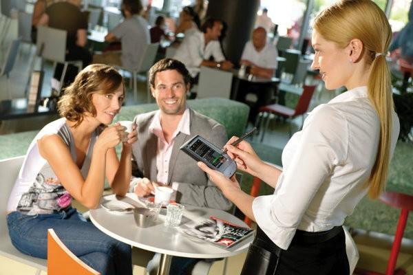 девушка-официант принимает заказ у молодой пары
