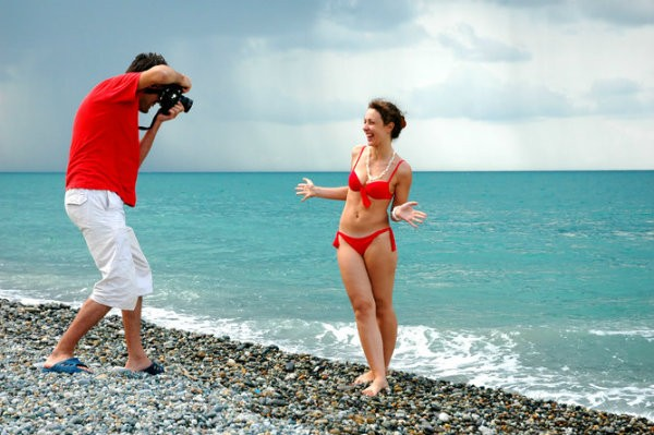 парень фотографирует девушку на фоне моря