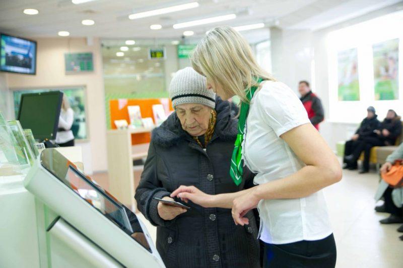 Работник Сбербанка помогает пенсионеру научится пользоваться кредиткой