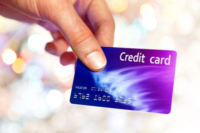 Держит в руке кредитную карту