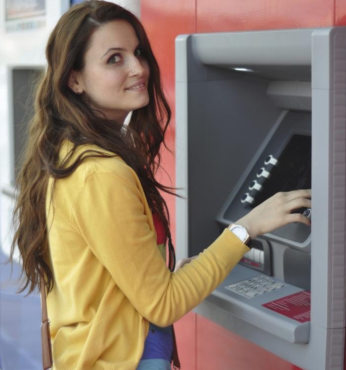 Девушка пополненяет счет через банкомат