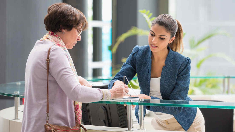 Сотрудник банка помогает клиенту активировать счет